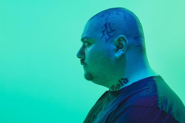 Portret van een man met kleurrijk neonlicht op groene achtergrond