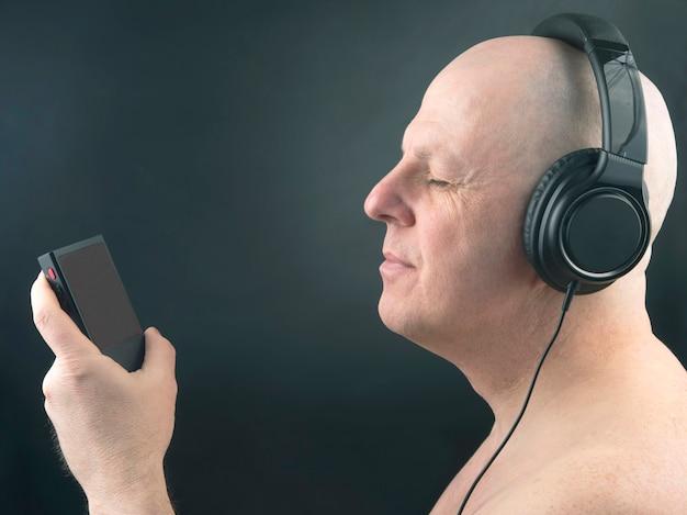 Portret van een man met koptelefoon en een speler die in ontspanning naar zijn favoriete muziek luistert