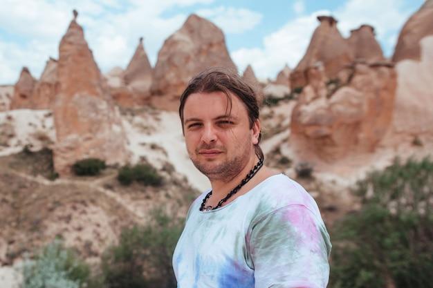Portret van een man met lang haar tegen de achtergrond van het reliëf van cappadocië