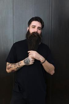Portret van een man met lange, bebaarde man tegen zwarte houten muur