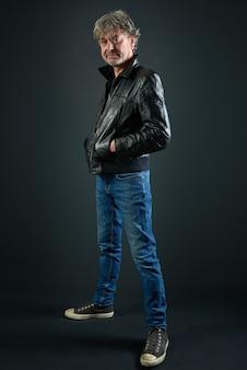 Portret van een man met leren jas en denim broek