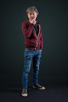 Portret van een man met rood shirt en denim broek