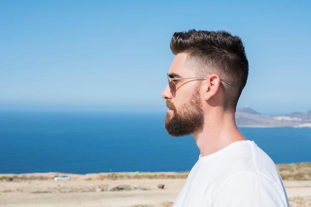 Portret van een man met zonnebril, een baard en een wit overhemd