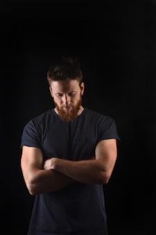 Portret van een man naar beneden kijken en met gekruiste en zwarte armen