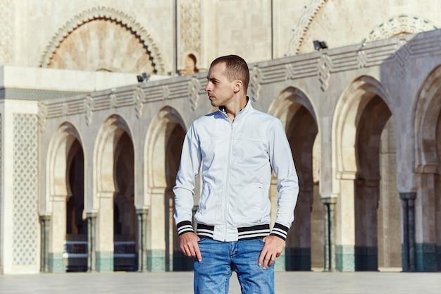 Portret van een man op de achtergrond van de hassan ii-moskee in marokko, casablanca