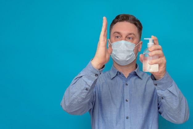 Portret van een man op een blauwe achtergrond die zeep of antibacteriële spray op zijn hand zuivert