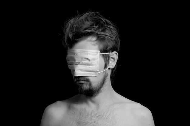 Portret van een man op een zwarte achtergrond, een masker op zijn ogen