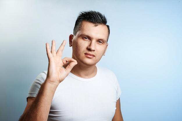 Portret van een man op lichte achtergrond, toont een hand ok, goedkeuring, lof.