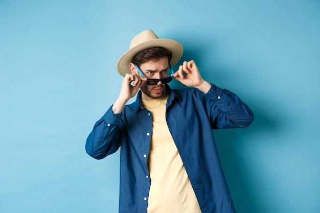 Portret van een man op vakantie opzij staren met geschokt en ineenkrimpend gezicht, zonnebril opstijgen en lege ruimte op blauwe achtergrond kijken.