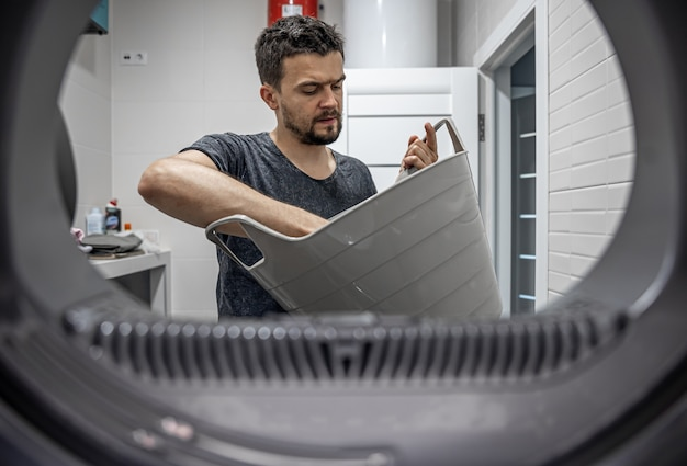 Portret van een man, uitzicht vanuit de wasmachine, laden en wassen van vuil linnen.