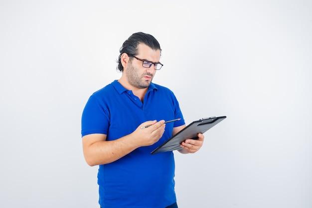 Portret van een man van middelbare leeftijd die naar klembord kijkt terwijl hij potlood in polot-shirt, bril vasthoudt en gefocust kijkt