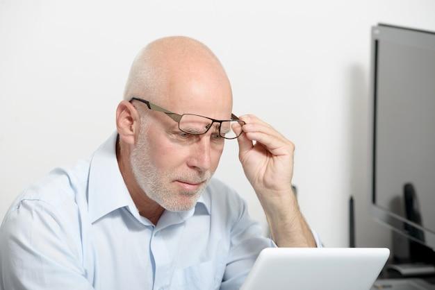 Portret van een man van middelbare leeftijd met een digitale tablet