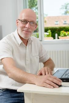 Portret van een man van middelbare leeftijd met laptop