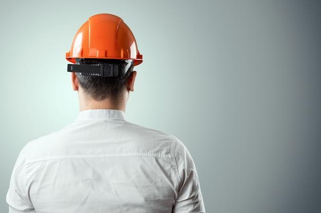 Portret van een man vanaf de achterkant in een constructie, oranje helm. conceptenarchitectuur, bouw, techniek, ontwerp, reparatie. ruimte kopiëren