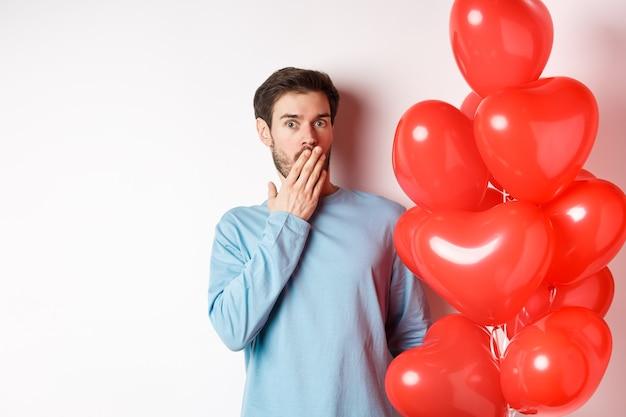 Portret van een man vriendje die in de buurt van valentijnsdag hartballonnen staat en naar adem snakkend geschokt, staande over een witte achtergrond bezorgd
