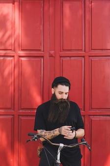 Portret van een man zit op de fiets met behulp van mobiele telefoon voor rode deur