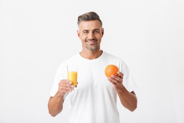 Portret van een mannelijke 30-jarige man met borstelharen die een casual t-shirt draagt met een glas sap en sinaasappelfruit op wit wordt geïsoleerd