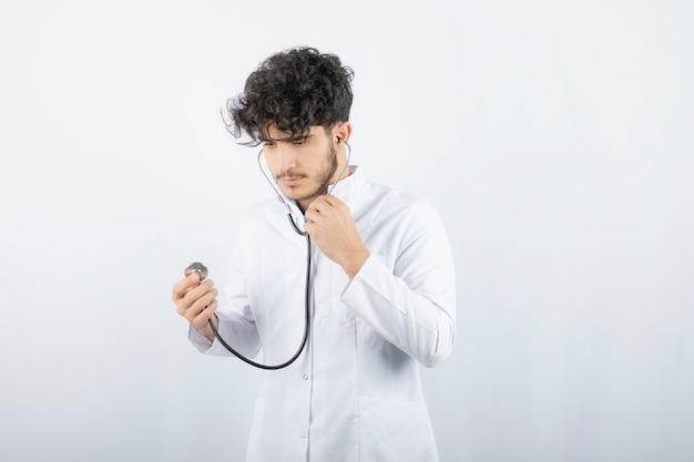 Portret van een mannelijke arts die een stethoscoop vasthoudt en luistert.