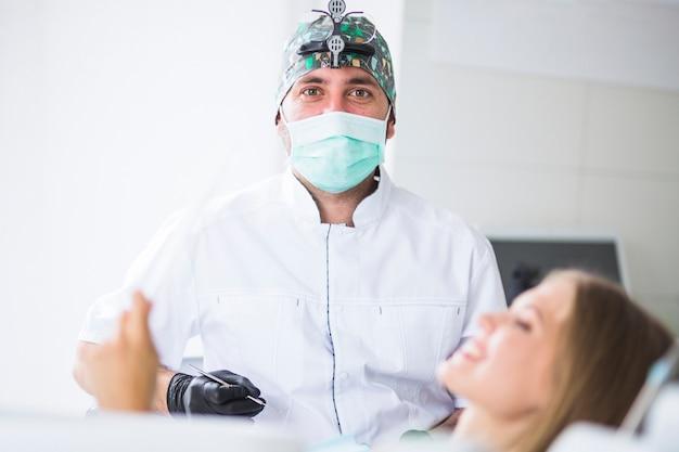 Portret van een mannelijke arts die masker draagt die vrouwelijke patiënt behandelt