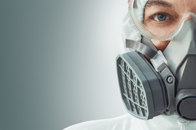 Portret van een mannelijke arts in een gasmasker, bril en een biologisch beschermingspak tegen coronavirusinfectie. covid19-bescherming.