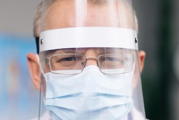 Portret van een mannelijke arts met een bril met een transparant beschermend gezichtsschildmasker en een overall in een ziekenhuiskamer bij de covid19