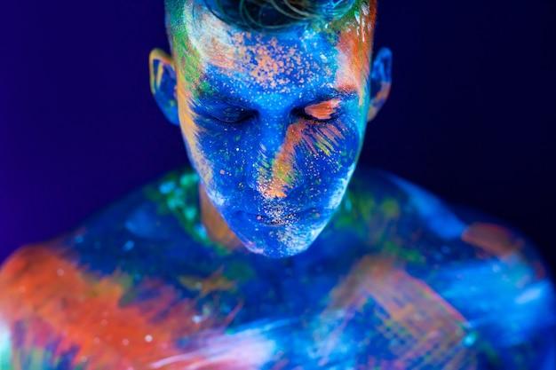 Portret van een mannelijke bodybuilder. de mens is geschilderd in ultraviolette kleuren