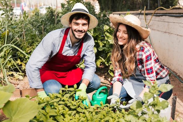 Portret van een mannelijke en vrouwelijke tuinman die in de tuin werken