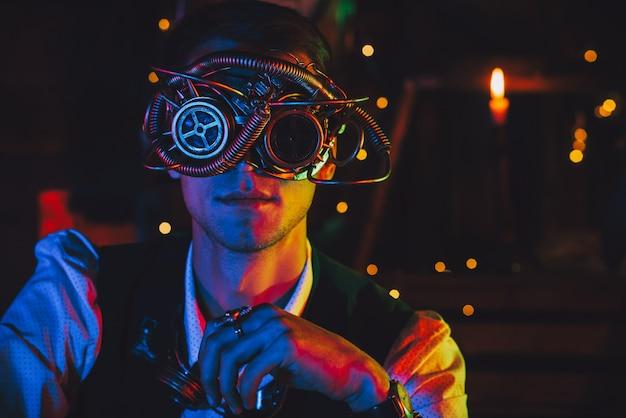Portret van een mannelijke ingenieur met een cyberpunkbril en een steampunkkostuum in een werkplaats met neonlicht