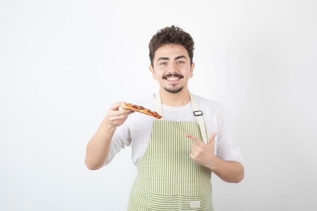 Portret van een mannelijke kok die een stuk pizza vasthoudt en ernaar wijst?