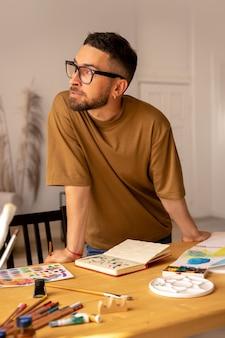 Portret van een mannelijke kunstenaar die bij een tafel staat en traint in een schilderles in een studio die een geeft