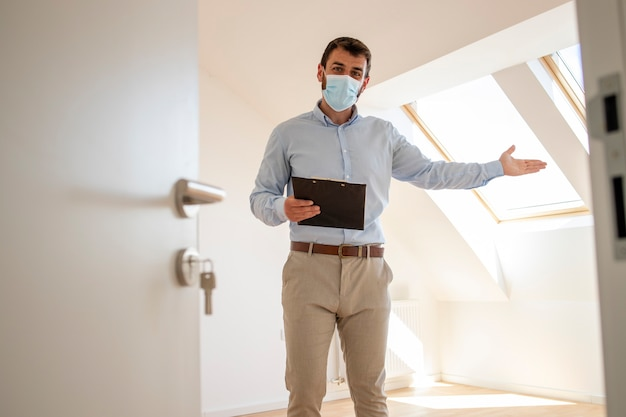 Portret van een mannelijke makelaar met gezichtsmasker die in een nieuw huis staat tijdens een pandemie van het coronavirus.