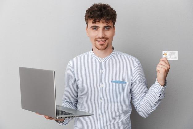 Portret van een mannelijke man gekleed in een overhemd glimlachend terwijl hij een zilveren laptop en creditcard vasthoudt die over een grijze muur is geïsoleerd