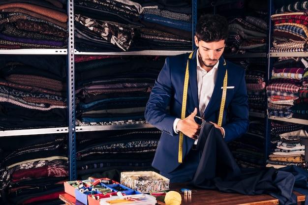 Portret van een mannelijke manierontwerper die de stof met schaar in zijn workshop snijdt