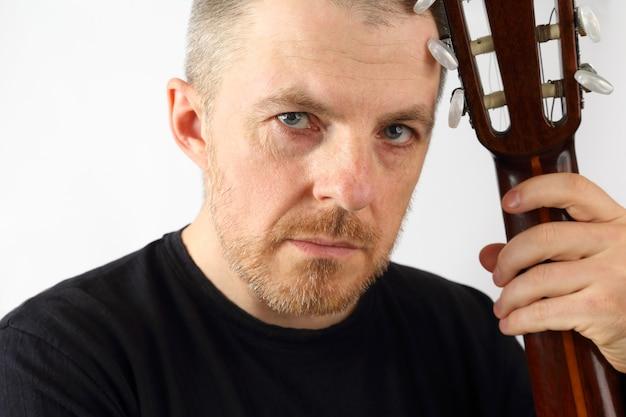 Portret van een mannelijke muzikant met een akoestische gitaar