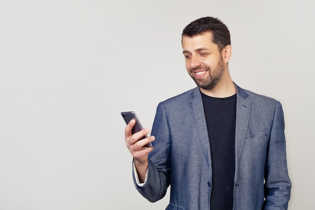 Portret van een mannelijke ondernemer die een smartphone in handen houdt die een bericht leest