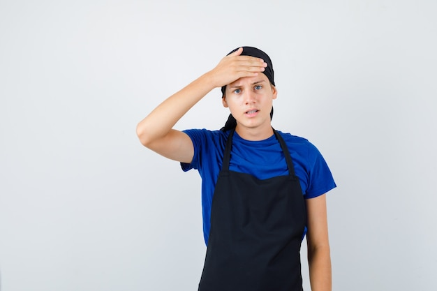 Portret van een mannelijke tienerkok die de hand op het voorhoofd houdt in een t-shirt, een schort en er gestrest vooraanzicht uitziet