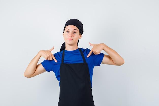 Portret van een mannelijke tienerkok die naar zichzelf wijst in t-shirt, schort en zelfverzekerd vooraanzicht