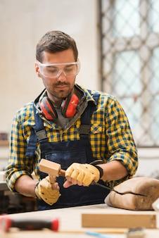 Portret van een mannelijke timmerman die houten vorm met beitel maakt
