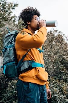 Portret van een mannelijke wandelaar die met zijn rugzak het water van fles drinkt