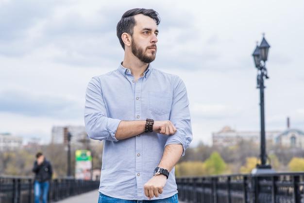 Portret van een manzakenman met een baard in een overhemd die zijn mouw rechtmaakt