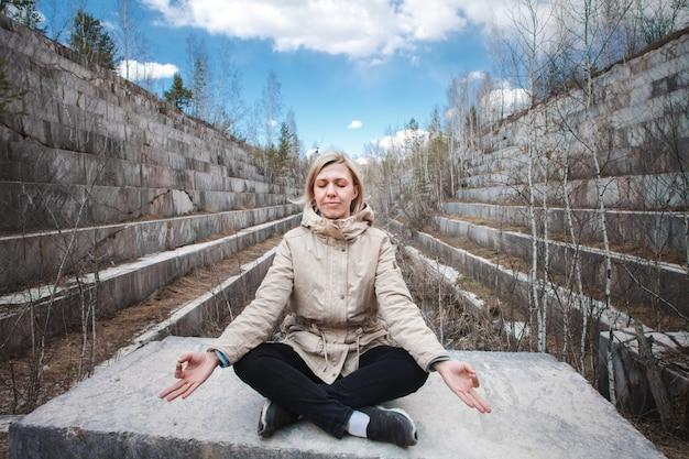 Portret van een mediterende blonde buitenshuis