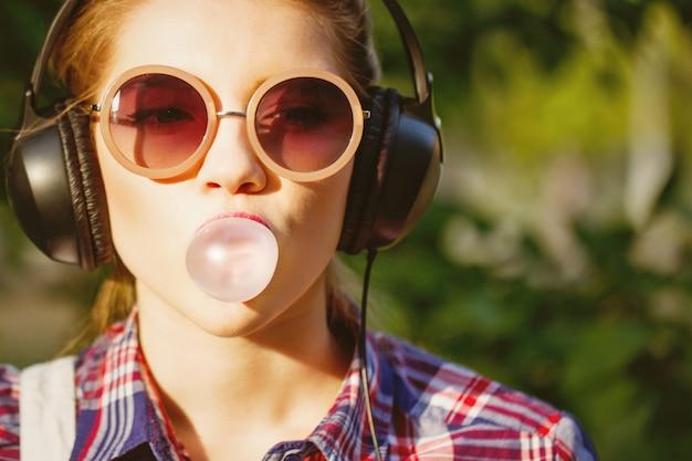 Portret van een meisje dat aan muziek op hoofdtelefoons luistert