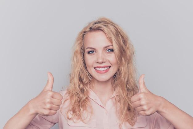 Portret van een meisje dat casual shirt draagt, heft twee duimen omhoog geïsoleerd op grijs