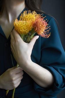 Portret van een meisje dat drie gele en oranje proteas houdt