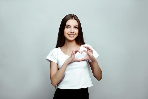 Portret van een meisje dat een hart met haar handen doet
