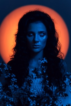 Portret van een meisje dat eruitziet als een nimf, in neonverlichting met een aureool boven haar hoofd en bloemen in haar handen. het concept van fantasie, sprookjes, fantasmagorie.