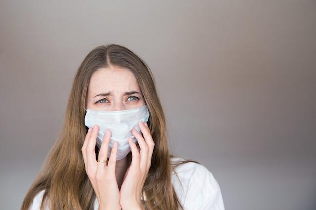 Portret van een meisje dat haar gezicht bedekt met een masker. angstige ogen van de patiënt.