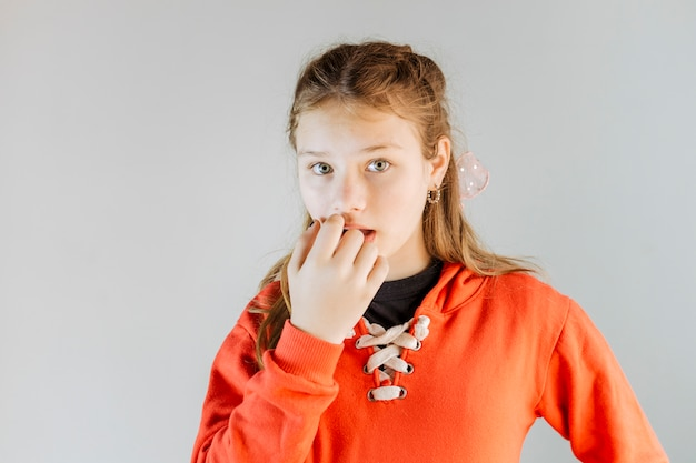Portret van een meisje dat haar vingernagels bijt