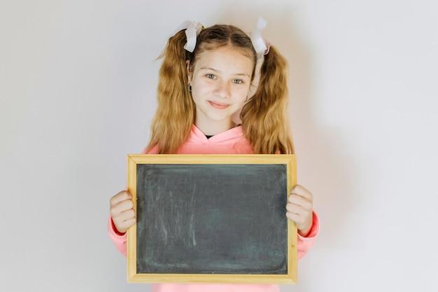 Portret van een meisje dat lege lei houdt