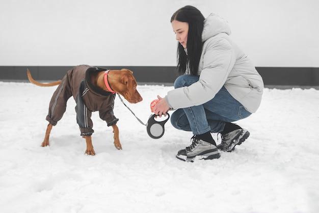 Portret van een meisje dat met een hond in het winterseizoen speelt.